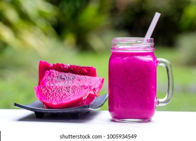 Fresh smoothies from a dragon fruit, banana, mango and papaya in glass mug. Island Bali, Ubud, Indonesia. Close up