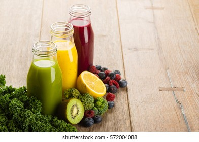 Fresh smoothies with fruits and vegetables on wooden background