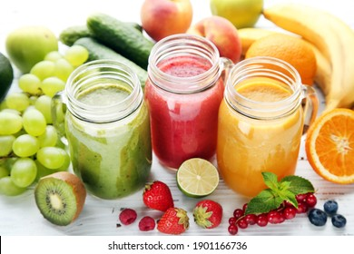 Fresh smoothies in glass jars with fruits and vegetables on wooden background
