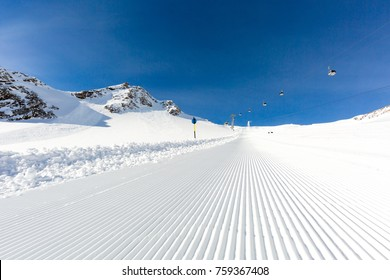 Fresh snow at recently groomed ski run at ski resort in the Alps on a sunny winter day.