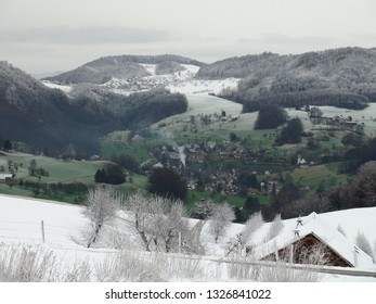 Fresh snow in winter landscape on the hills of the swiss Jura. Reigoldswil in the valley. CH Switzerland