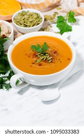 fresh soup of pumpkin and lentils on white background, vertical closeup