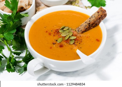 fresh soup of pumpkin and lentils on white background, closeup horizontal