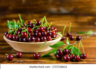 Fresh sour cherries in a wooden bowl and green leaves on the board. Fresh ripe sour cherries.