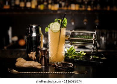 Fresh and sour tasty yellow summer cocktail with ginger, cucumber and mint among bar utensils on dark background