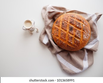 Fresh sourdough starter and homemade bread on white background