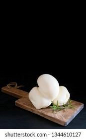 Fresh southern Italian traditional Scamorza semi-soft cow cheese on a black background, ready to eat with copy space. Scamorza is a very popular cheese in Puglia
