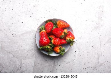 Fresh spanish strawberries in a bowl on a rustic table, top view
