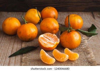Fresh spelled clementine tangerines with leaves close-up on wooden background