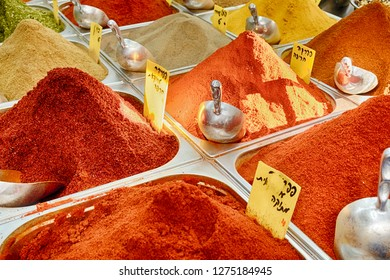 Fresh spices in a Jerusalem spice market are heaped high in a series of metal bins.