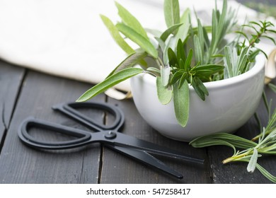 fresh spices and ribbon, scissors on black wooden table background