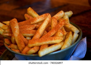 Fresh spicy French fries with chili and Cajun seasoned powder in a bowl