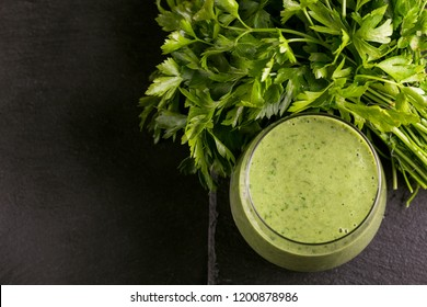 Fresh spinach and avocado smoothie in glass with parsley on black slate background. Top view. Copy space