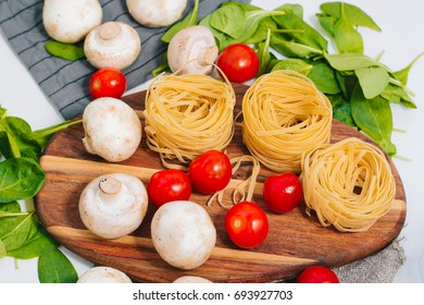 Fresh spinach and cherry tomatoes with mushrooms and pasta. Raw vegetable. natural plant leaf. healthy and vegetarian or organic bio food. close up