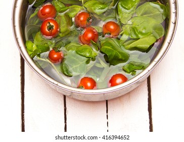 Fresh spinach and cherry tomatoes in a pan of water on a white wooden background
