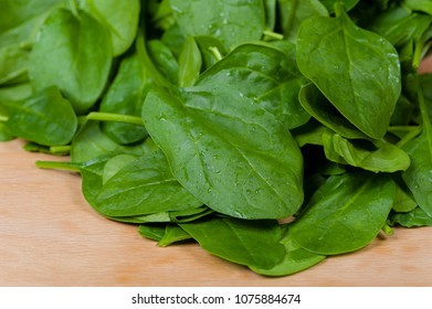 fresh spinach displayed on a wooden table
