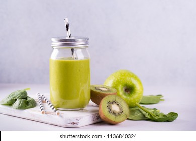 Fresh spinach and fruit green smoothie with ingredients on light background