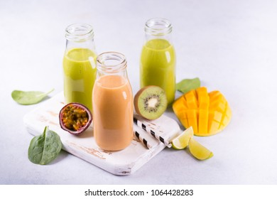 Fresh spinach and fruit green smoothies with ingredients on light background