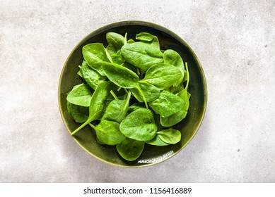 Fresh spinach. Green vegetable leaves on plate, healthy food, vegan diet concept.