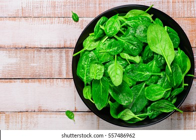 Fresh spinach leaves in a black bowl on the old wooden background.