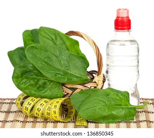Fresh spinach leaves with bottle of water over white background