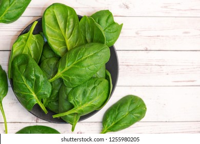 Fresh spinach leaves in bowl on dark background. Top view. With Copy Space.
