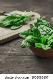 Fresh spinach leaves in a bowl on a rustic wooden table. Selective focus.