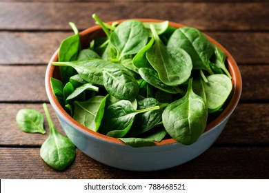 Fresh spinach leaves in bowl on rustic wooden table. Selective focus.