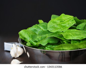 Fresh spinach leaves in metallic bowl over dark background