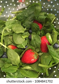 Fresh spinach leaves strawberries and blueberries