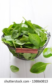 Fresh spinach leaves in a vintage metal basket on a white wooden background