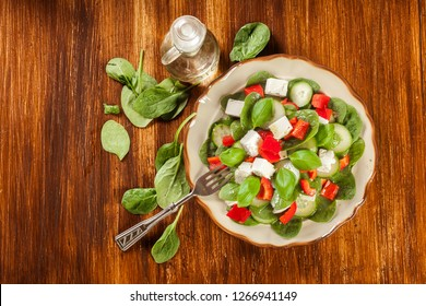 Fresh spinach salad with feta, cucumber and red paprika on a plate. Healthy raw food concept. Top view.