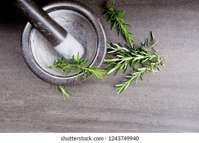 Fresh sprigs of Rosemary herb leaves with marble mortar and pestle on gray / grey slate background