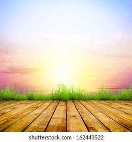 Fresh spring green grass with nice sky sunlight and wood floor. Beauty natural background