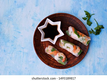 Fresh spring rolls in rice paper with shrimp, vegetables and rice noodles on a brown clay plate on a light blue background. Vietnamese cuisine. Healthy food. Selective focus