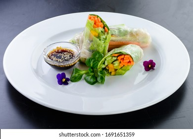 Fresh spring rolls, rice paper rolls, summer rolls with edible flowers. vegetable spring rolls decorated with flowers