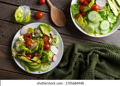 Fresh spring salad with lettuce, cucumber, cherry tomatoes, radishes, spring onion and avocado topped with balsamic glaze and extra virgin olive oil. Natural dark wooden background.