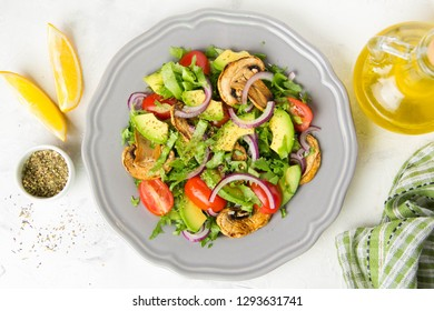 Fresh spring salad with mushrooms, cherry tomatoes, avocado and onions. Delicious vegetarian lunch, healthy food