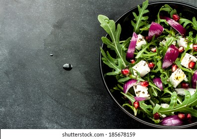 Fresh spring salad with rucola, feta cheese, red onion and pomegranate seeds in black bowl on chalkboard background with free text space.