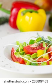 Fresh spring salad. tomatoes, yellow and green pepper, Sunflower sprouts in a bowl on a white background