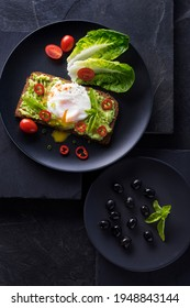 Fresh spring sandwich on a sliced gluten free sunflower bread. Red and green vegetables on black slate stone. Poached egg, avocado, chilli and spring onion garnished with plum tomatoes