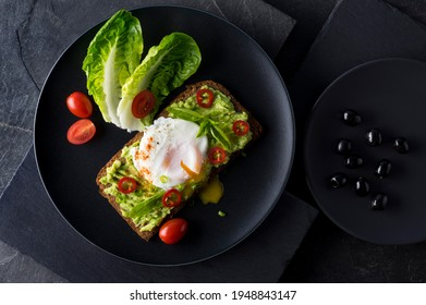 Fresh spring sandwich on a sliced gluten free sunflower bread. Red and green vegetables on black slate stone. Poached egg, avocado, chilli and spring onion garnished with plum tomatoes and black olive