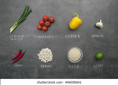 Fresh spring vegetables, white beans and rice with chalky signs on grey kitchen table. Top view, flat lay food concept.