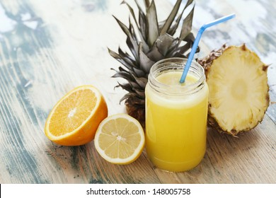 Fresh squeezed orange,lemon and pineapple juice arranged with fruits on wooden rustic table. Shot at daylight, shallow depth of field.