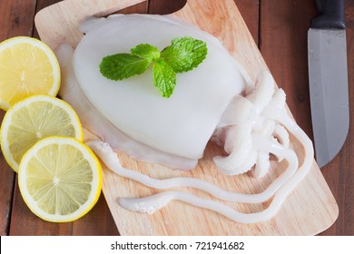 Fresh squid placed on a cutting board waiting for cooking with Knife for slicing, with lemon decorated.All on a wooden desk.
