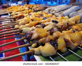 Fresh squids skewer stacked on street food market.