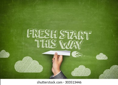 Fresh start this way concept on green blackboard with businessman hand holding paper plane
