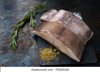 fresh steak raw fish halibut on the stone with the salt and herbs on steel background