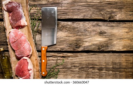 Fresh steak from raw meat and spices and chopping knife. On wooden background. Free space for text . Top view