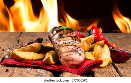 Fresh steaks with flames on background